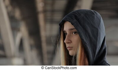 A close up of a teenage girl in a hoody with the hood on and loose multicolored hair spread in the wind under the unfocused bridge pillars watching the car passing by.