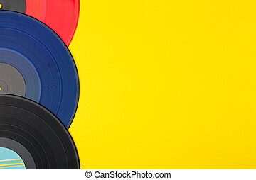 A close up of a three colorful vinyl records lie on a yellow background
