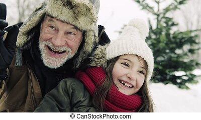 A close-up of grandfather and small girl in snow on a winter day.