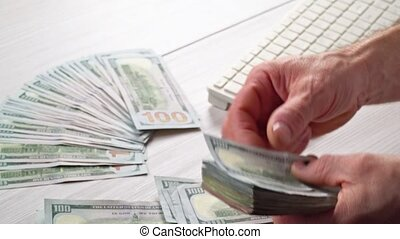 A Close up of male hands counting US dollar banknotes man is counting the US money