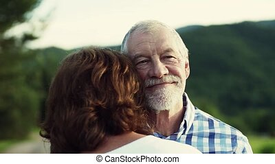 A close-up of senior couple in love standing outdoors in nature, hugging.