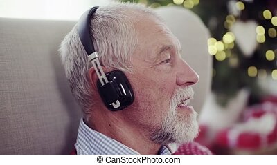 A close-up of senior man with headphones at home at Christmas time, singing.