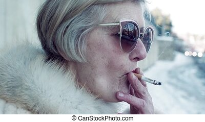 A close-up of senior woman standing outdoors in town, smoking a cigarette.