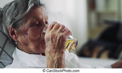 A close-up of sick senior woman lying in bed at home, drinking.