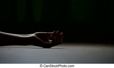 A close-up of the girls hand is lying lifeless on the floor...