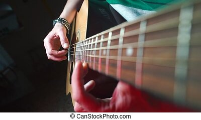 A close-up of the hands of a composer playing an acoustic guitar.