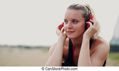 A close-up of young woman runner with headphones resting outside by the sea.