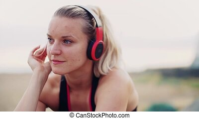 A close-up of young woman runner with headphones resting...
