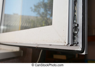 A close-up on a plastic window profile corner with a locking mechanism and a seal.