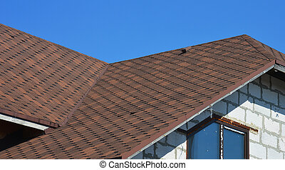 A close-up on a roofing construction of a brick house covered with asphalt shingles with roofing flashing installed in problem areas.