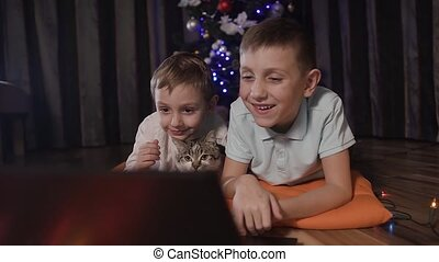 A close up - on the background of a blurred Christmas tree, two brother and their little cat are lying on the floor on the room and looking at something interesting on the laptop through a social network