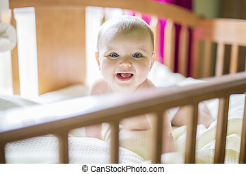 Close-up portrait of a cheerful cute baby in the crib at home