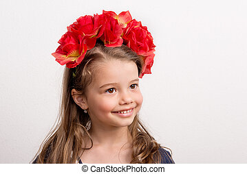 A close-up portrait of a small girl in studio wearing red flower headband.