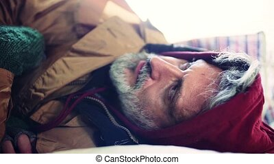 A close-up portrait of homeless beggar man lying outdoors. -...
