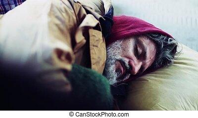 A close-up portrait of homeless beggar man lying outdoors. -...