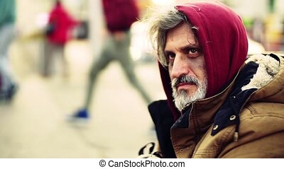 A close-up portrait of homeless beggar man sitting outdoors on the street. Slow motion.
