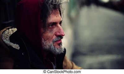 A close-up portrait of homeless beggar man sitting outdoors....