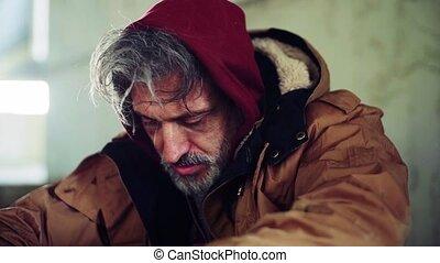 A close-up portrait of homeless beggar man sitting outdoors....