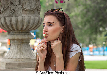 a close-up portrait of young attractive brunette with lollipop