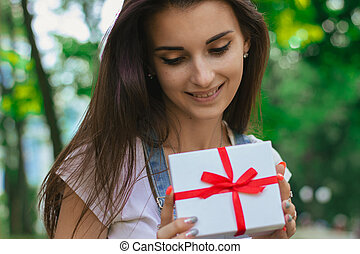 a close-up portrait of young charming girl with a gift