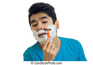 a close-up portrait of young man who stands with foam on your face and shaves his beard