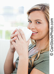 A close up shot of a smiling woman looking in front of her with a cup to her lips.