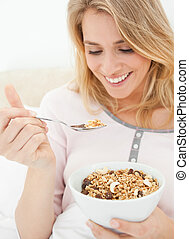 A close up shot of a woman holding a bowl of cereal and a raised spoon of cereal near to her mouth.