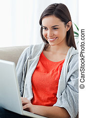 A close up shot of a woman looking at her laptop screen while lying on the couch