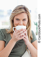 A close up shot of a woman looking forward, as she holds a mug up in front of her mouth.