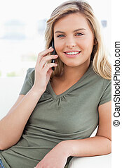 A close up shot of a woman making a call while smiling and looking in front of her.
