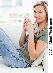 A close up shot of a woman sitting sideways on the couch, with a mug in hand raised to her lips, as she smiles and looks forward.