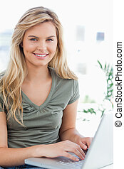 A close up shot of  a woman smiling and looking in front of her as she uses a laptop on the couch.