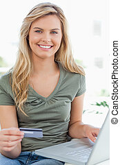 A close up shot of a woman smiling as she looks forward and uses her credit card and and laptop.