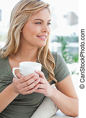 A close up shot of a woman with her head turned to the side while holding a mug in her hands and smiling.