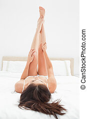 A close up shot of a woman with her legs raised fully...