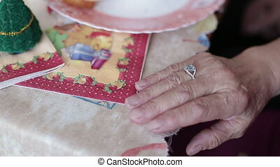 A close up shot of an elderly lady's clasped hands with her wedding ring in view.