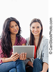 A close up shot of two smiling women looking at the camera and holding a tablet pc