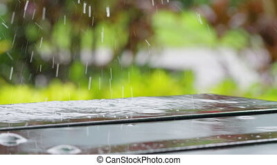 A close up shot of water drops on bench