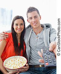 A close up shot with focus on the couple sitting on the couch with popcorn as they use a remote to change the tv