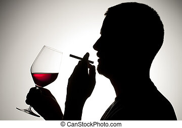 silhouette of a man smoking and drinking wine