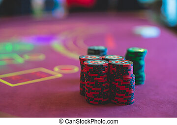 A close-up vibrant image of multicolored casino table with roulette in motion, with casino chips. the hand of croupier, mone and a group of gambling rich wealthy people in the background