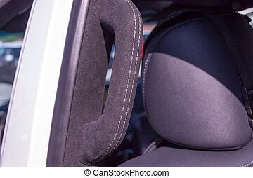 A close-up view of a black plastic handle on the ceiling in a car in a passenger seat pulled by a black soft leather cloth in the workshop of a tuning studio
