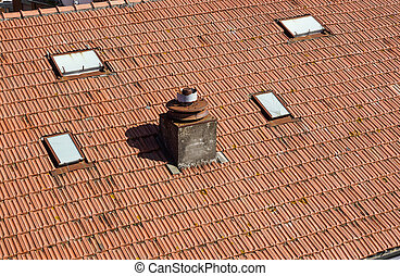 A close up view of a chimney on top of red roof tiles
