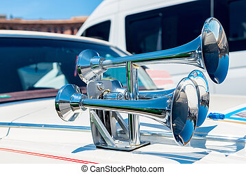 A close-up view of a chrome horn on the hood of a car