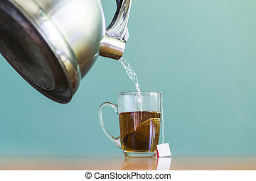A close up water pouring into glass cup tea