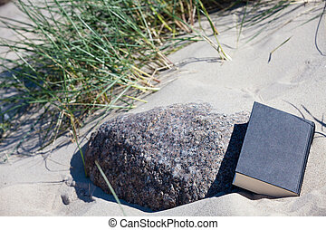 A closed book lies in the sand at a stone