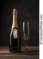 A closed bottle of champagne and an empty wine glass on a wooden background.