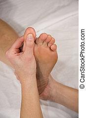 foot reflex zone massage - a closeup of a foot of a natural...