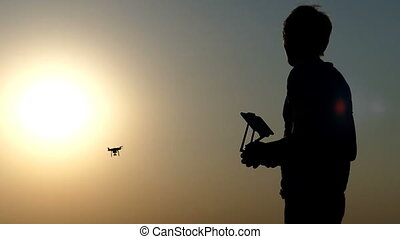 A closeup of a man, control panel, and a flying drone at sunset