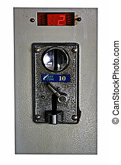 A closeup of a metal coin slot panel from a coin operated machine with entry and exit slots and button on an isolated background